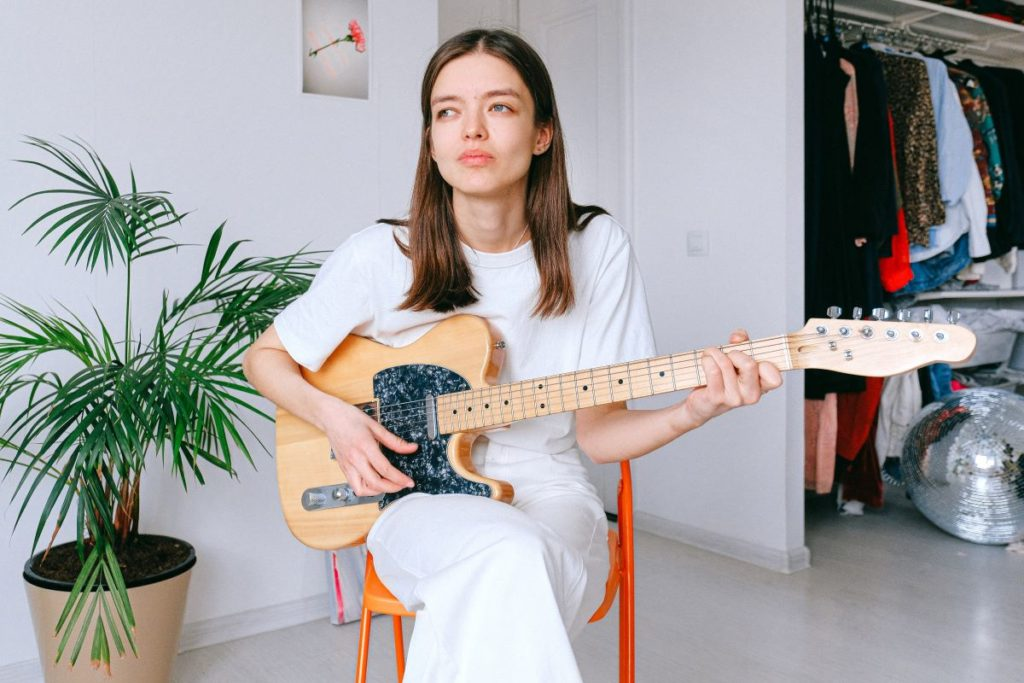 woman holding a fender telecaster guitar