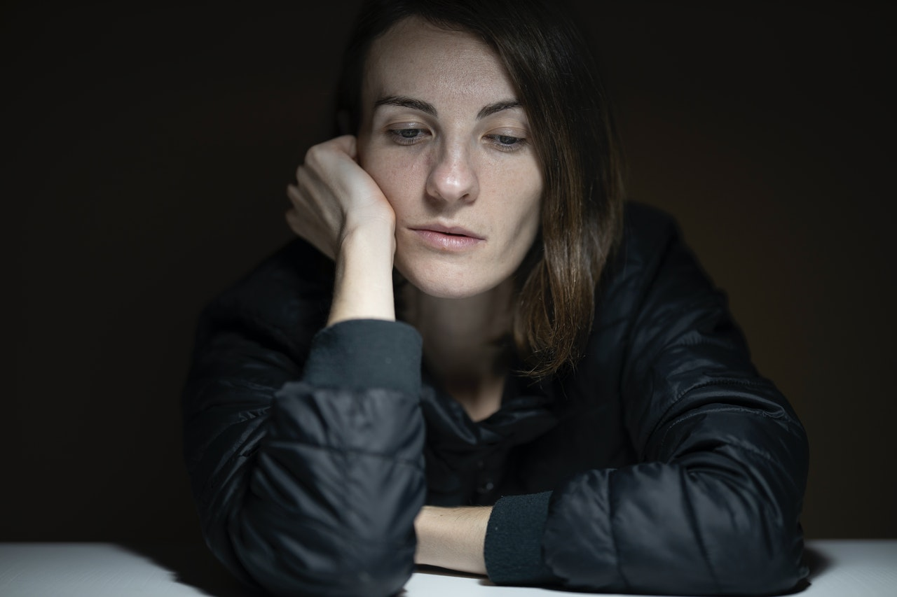 woman resting her head on her hand looking depressed