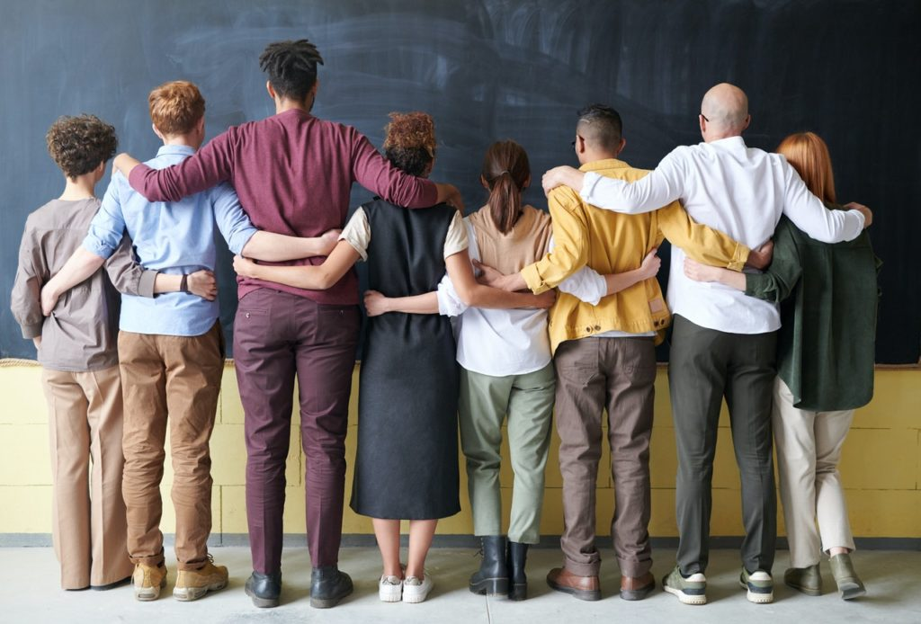 diverse group of people facing chalk board
