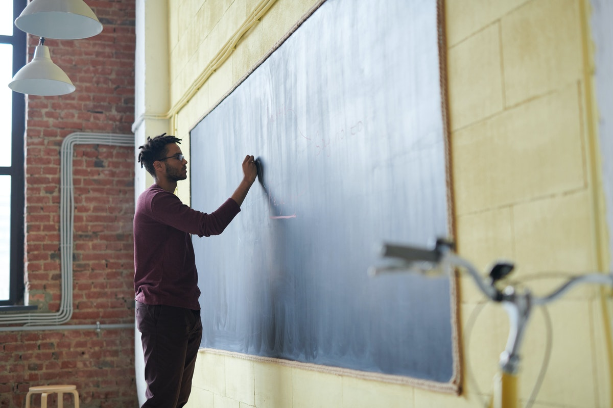 teacher writing on a blackboard
