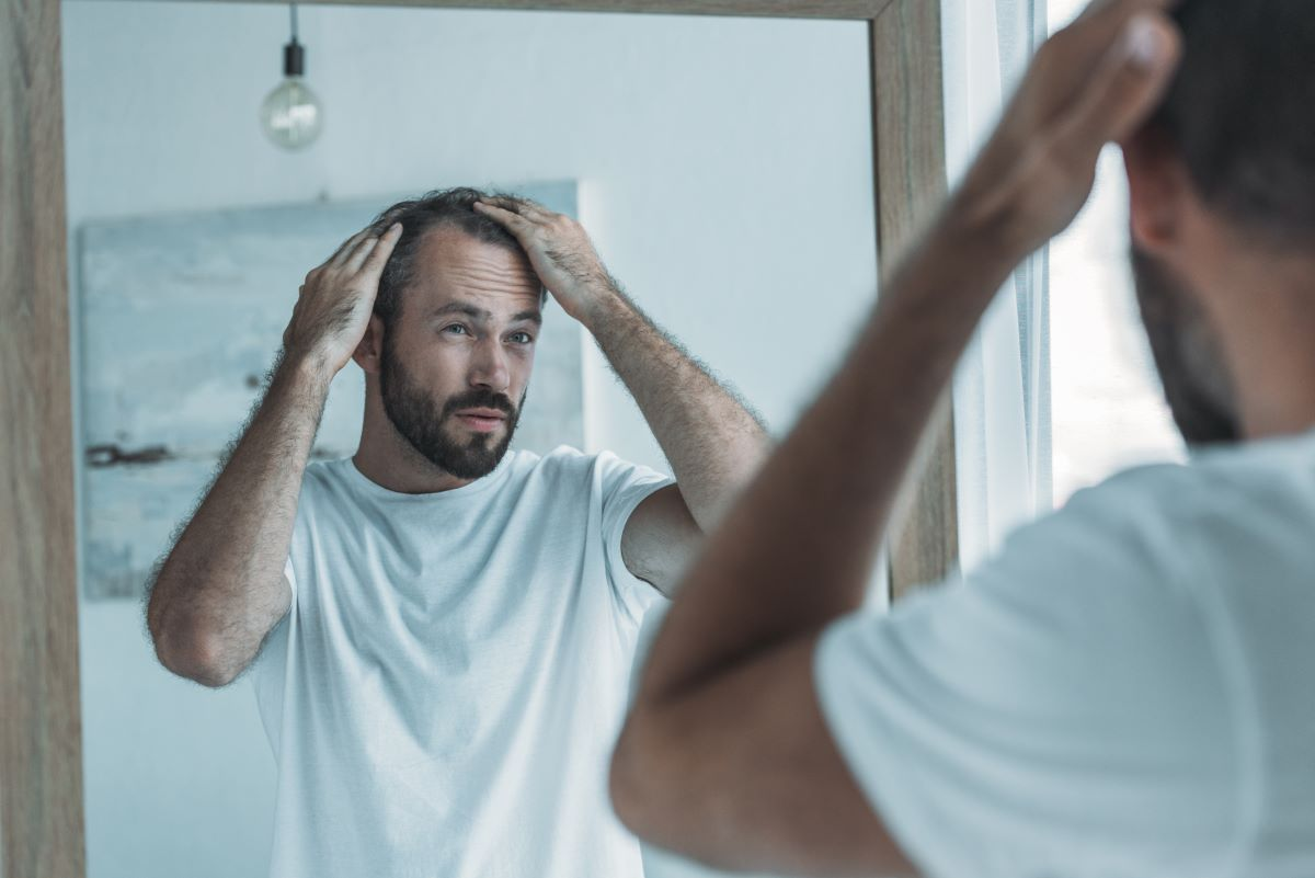 man looking in the mirror touching his hair