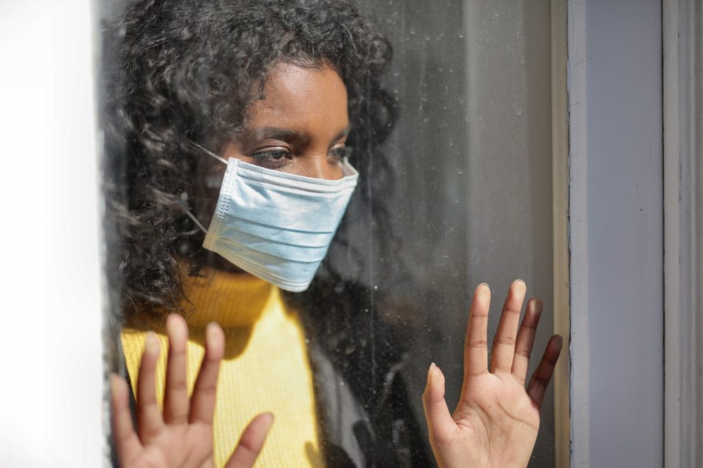 woman wearing facemask looking outside window