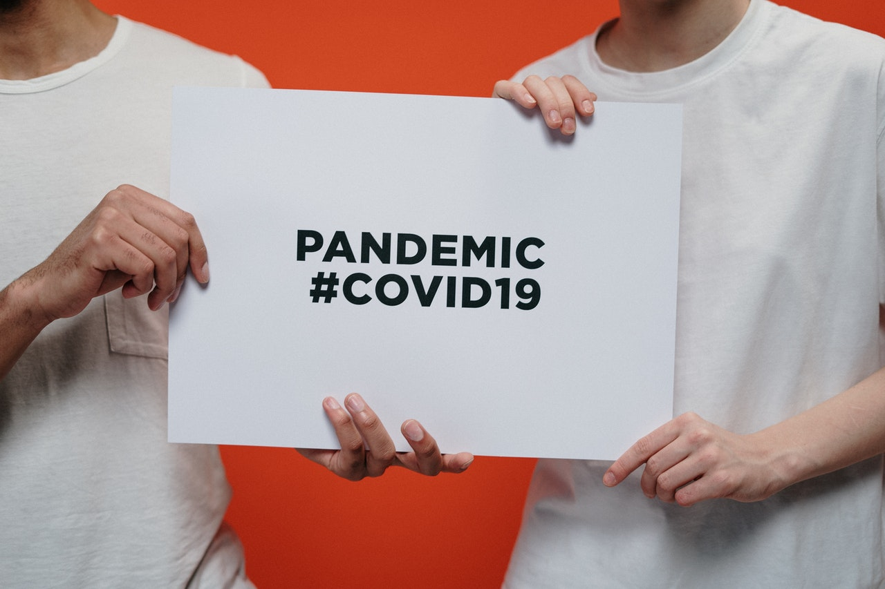holding sign that says pandemic #covid19