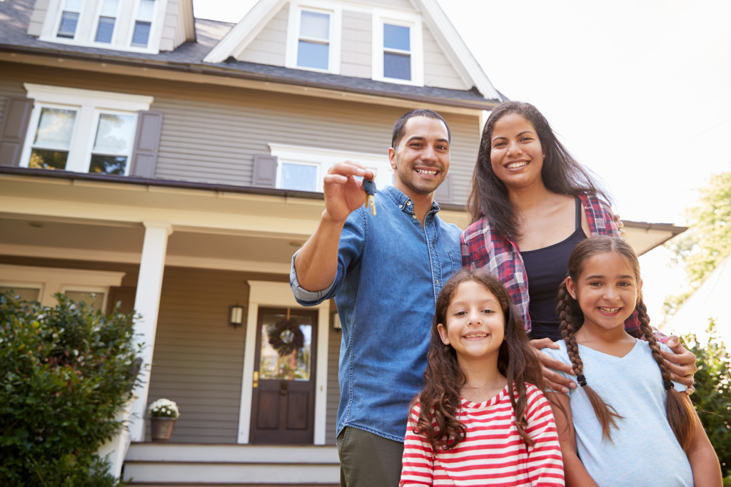family posing in front of ytheir newly bought house