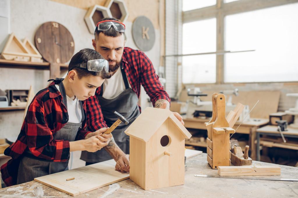 man and son building birdhouse