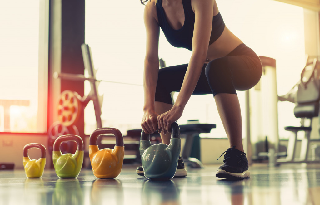 woman exercising trying to lift a kettlebell